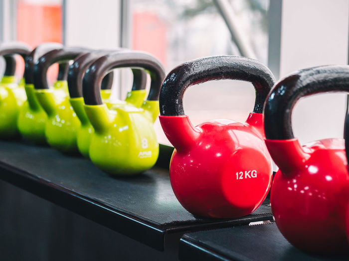 Rows of heavy metal dumbbells on rack in the gym or club. Weight Training Equipment. Sport and health concept. Arrangement Choice Close-up Collection Container Dumbbell Focus On Foreground Food And Drink Green Color Group Of Objects In A Row Indoors  Multi Colored No People Pepper Red Side By Side Still Life Table Variation Vegetable Weight Training
