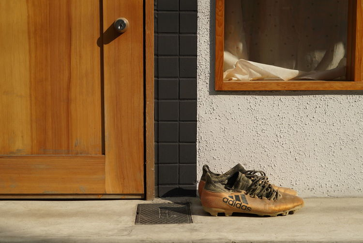 Low angle view of shoes on window of house