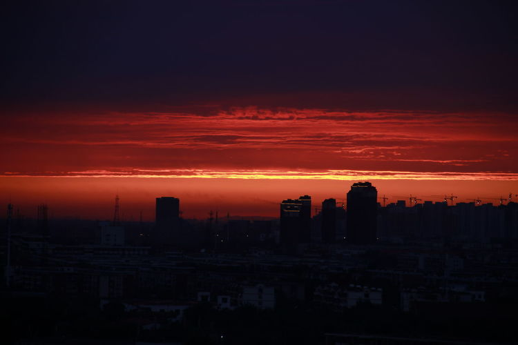 Silhouette Cityscape Against Dramatic Sky During Sunset