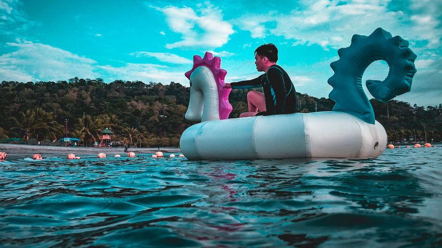 Man on pool raft floating on sea against sky