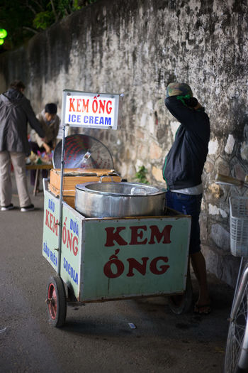 Vendor standing with ice cream stand by wall