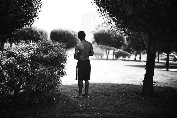 Rear view full length of shirtless man standing at park