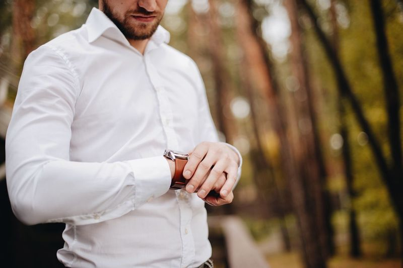 Midsection Of Young Man Checking Time While Standing Against Trees In Forest