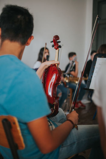 Man holding violin while sitting in classroom
