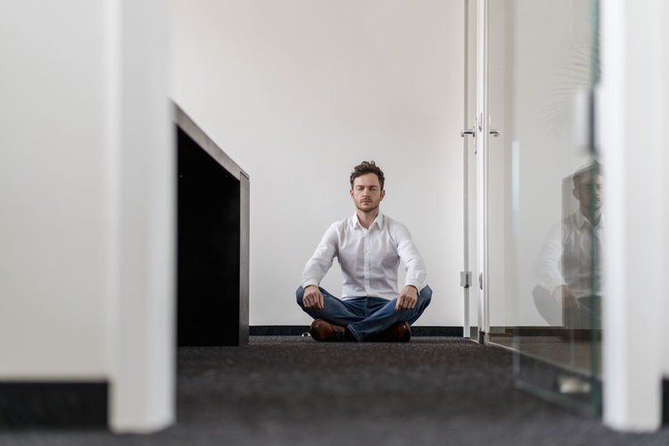Portrait of young man sitting on floor