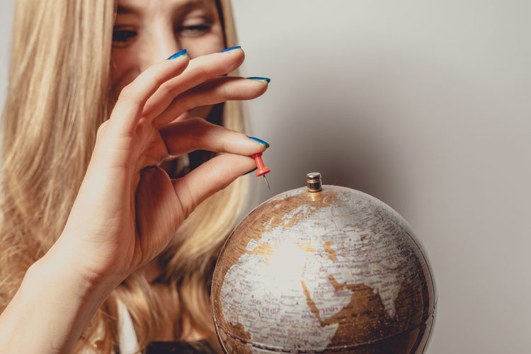 Woman Looking At Globe Against Gray Background