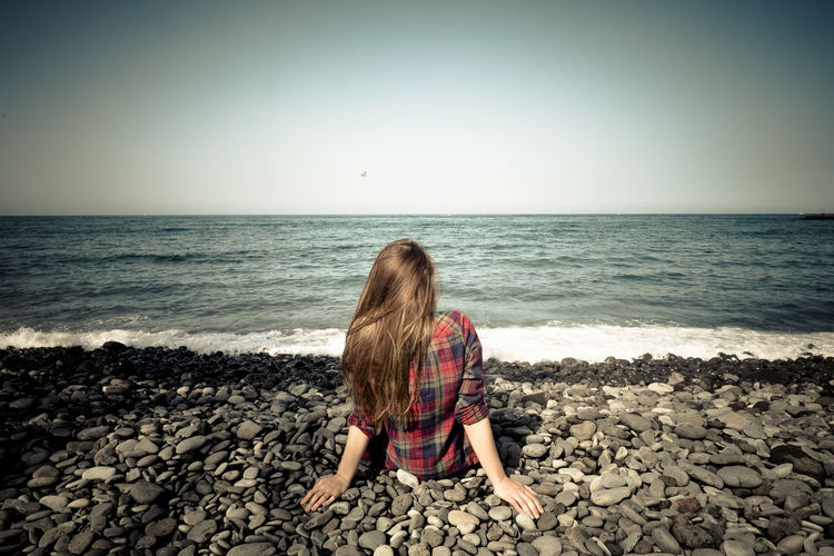 Rear view of woman sitting on rock at beach against clear sky