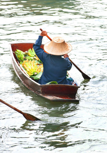 Rear View Of Person With Food Sitting In Boat On Lake