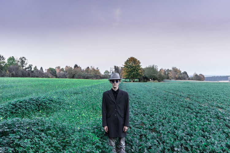 Portrait of young man wearing coat and hat while standing on agricultural field against sky