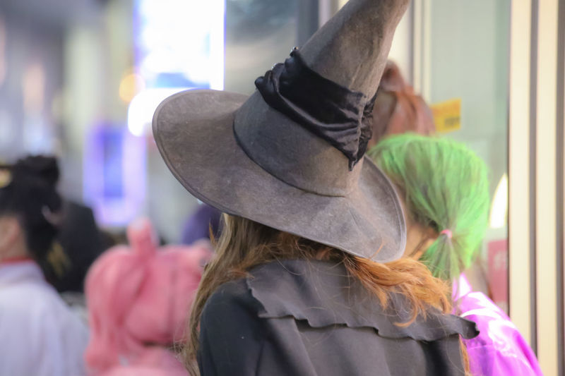 Rear view of woman wearing witch hat during halloween