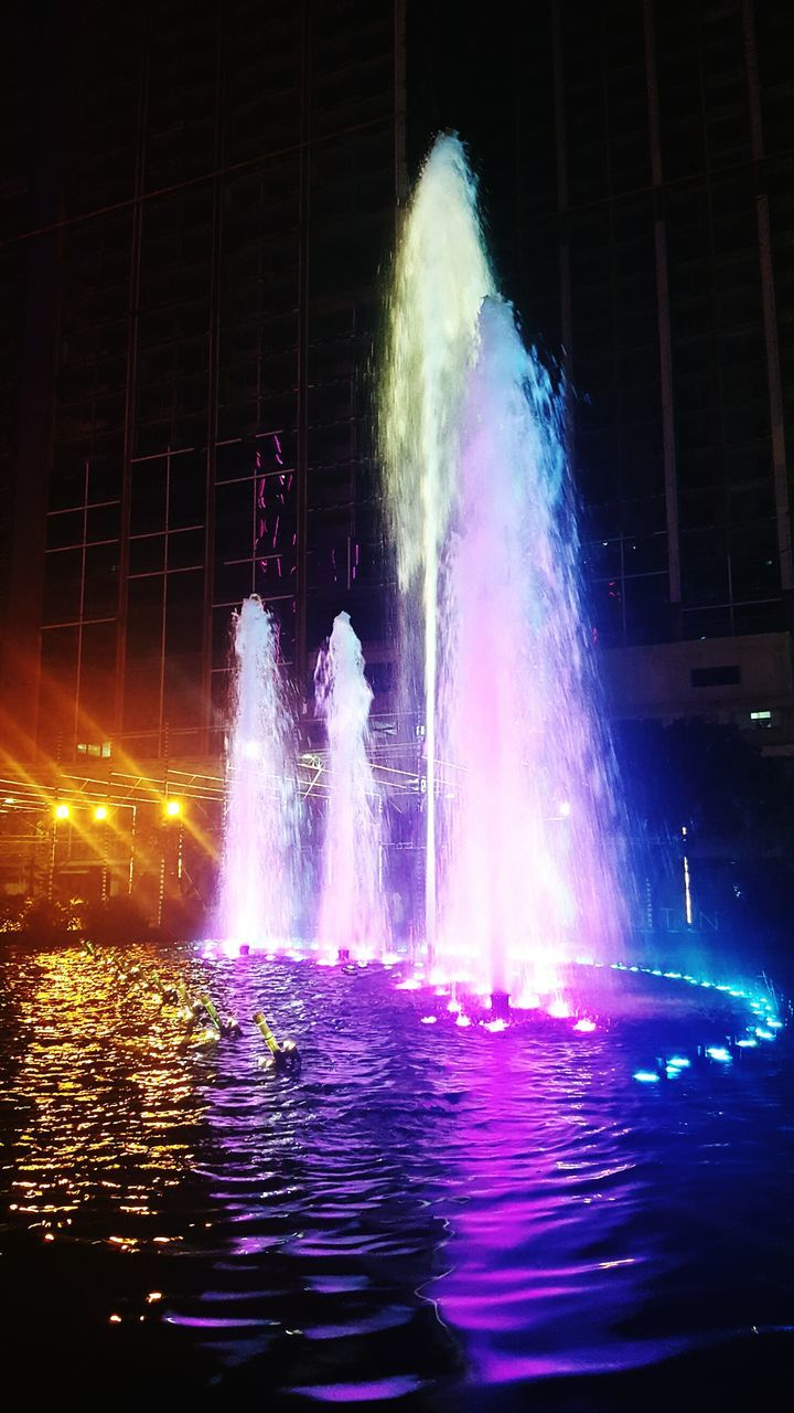 night, celebration, real people, outdoors, long exposure, illuminated, motion, women, spraying, water, multi colored, men, architecture, people