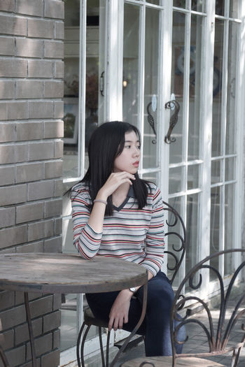 Thoughtful young woman sitting on chair at outdoor cafe