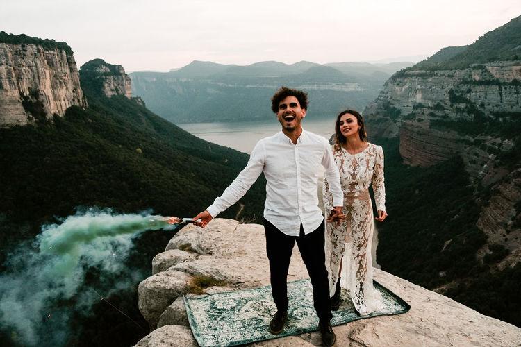 Portrait of happy friends standing on rock