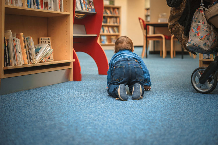 Baby Escaping Library Rear View Baby Boy Bookshelf Boy Casual Clothing Childhood Denim Full Length Indoors  Low Section Multi Colored Rear View