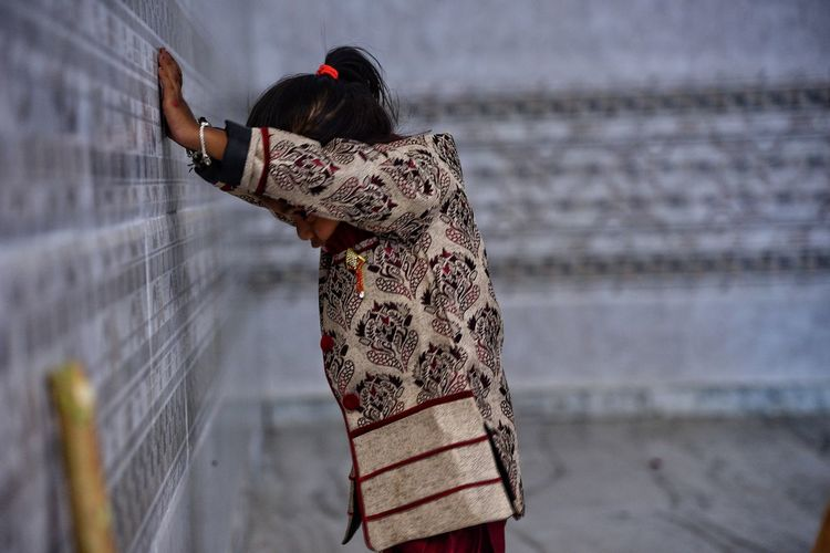 Side View Of Girl Standing By Wall