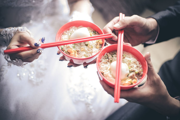 Close-Up Of Hands Holding Noodle Soup