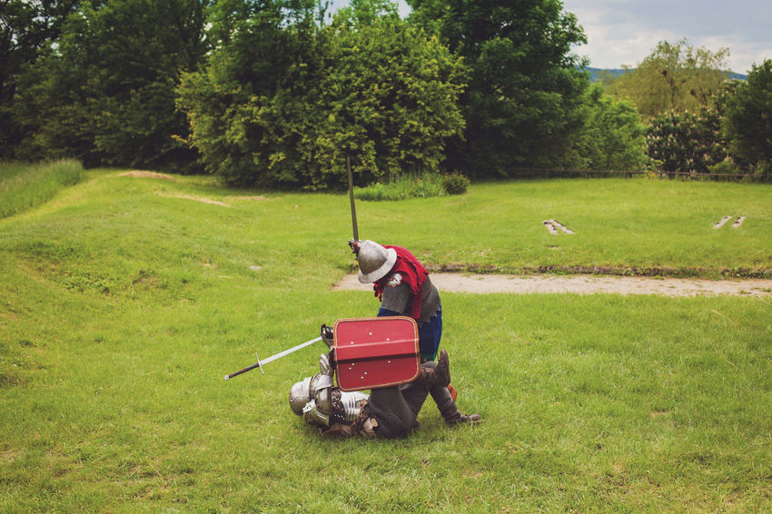 Two medieval knights in armor with swords and helmets are fighting on green grass Adults Only Battle Competition Fighting Grass Helmets Knights Meadow Medieval Only Men Outdoors People Protection Summer Sward Tournament Tree The Photojournalist - 2017 EyeEm Awards