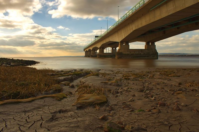 Bridge - Man Made Structure Connection Architecture Built Structure Sky Water Cloud - Sky Transportation River Beach Outdoors Nature Bridge Horizon Over Water Day No People Underneath