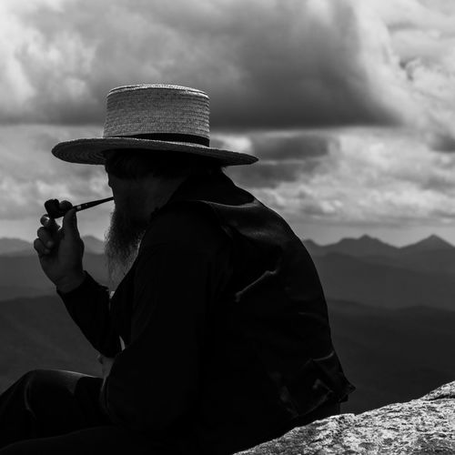 Man holding hat while sitting against mountains against sky