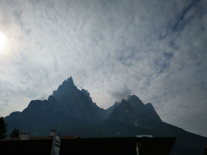 Low angle view of buildings and mountains against sky