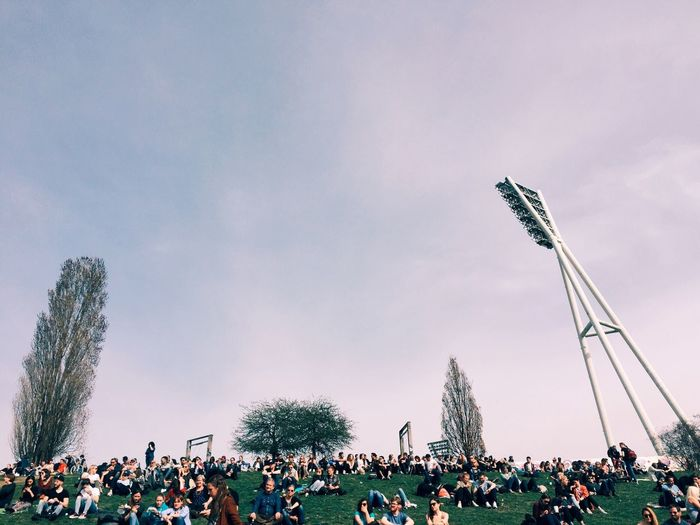 People on grassy field against sky at mauerpark