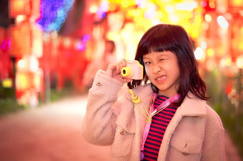 Portrait of cute girl photographing in illuminated carnival