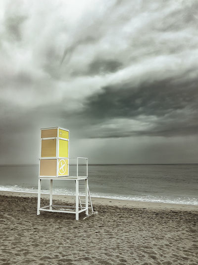 Lifeguard tower on a cloudy day Cloud - Sky Sky Sea Beach Water Land Horizon Over Water Sand Horizon Beauty In Nature Scenics - Nature Nature Overcast Communication Sign Storm Safety Tranquil Scene No People Outdoors Ominous Lifeguard Hut Lifeguard