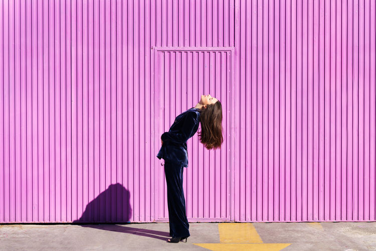 Side view of woman standing against pink wall