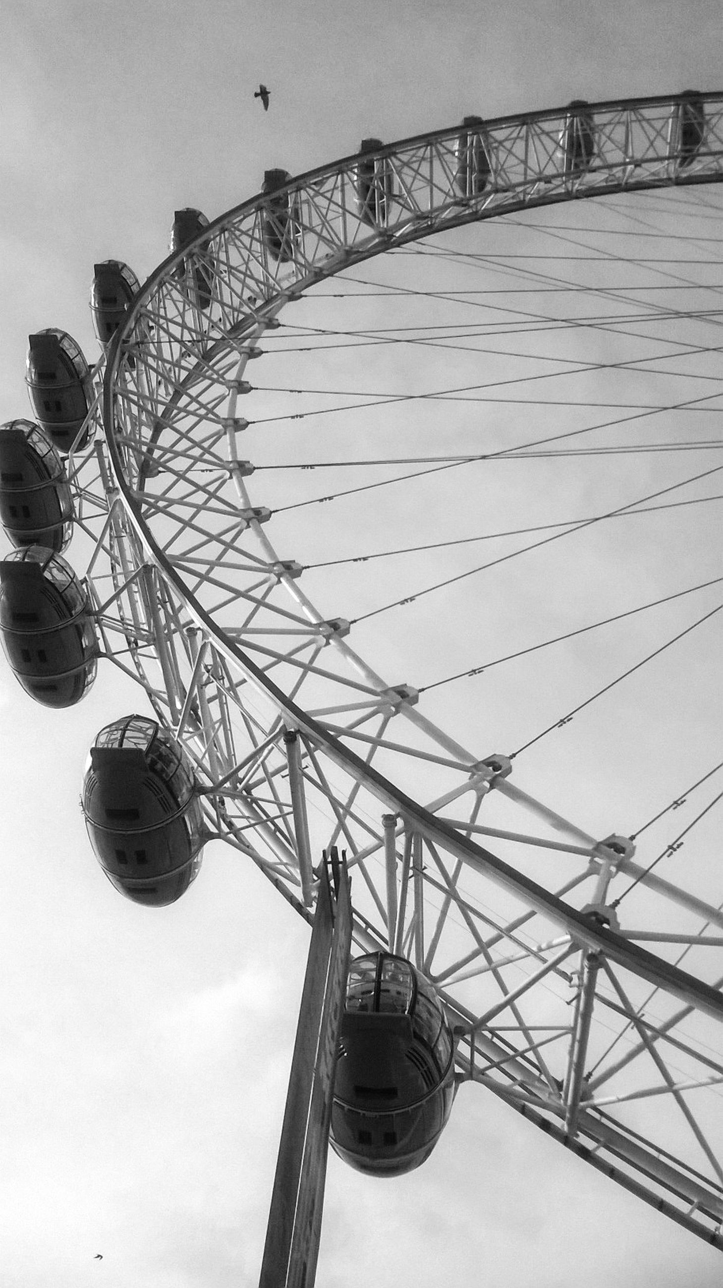 low angle view, built structure, ferris wheel, architecture, amusement park ride, amusement park, arts culture and entertainment, sky, metal, connection, engineering, bridge - man made structure, day, outdoors, tall - high, travel destinations, famous place, building exterior, incidental people, no people