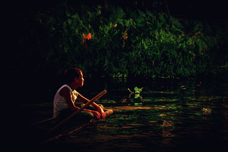Gazing boy on the boat Tree Water Lake Side View Sitting Tranquility Sunset Horizon Over Water