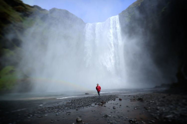Man Walking Against Waterfall During Foggy Weather