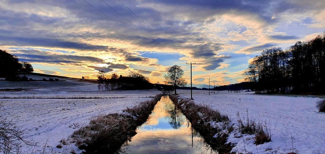 Scenic view of snow covered canal against sky