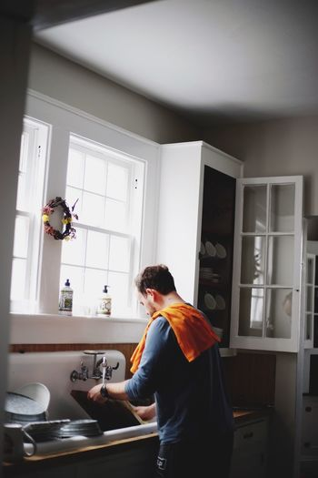 Man washing utensils in kitchen