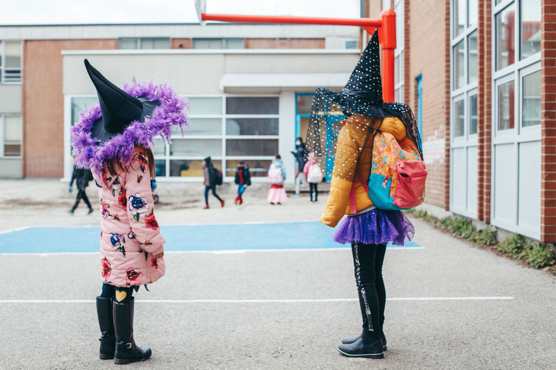 Full length of girls wearing costume standing in front of building