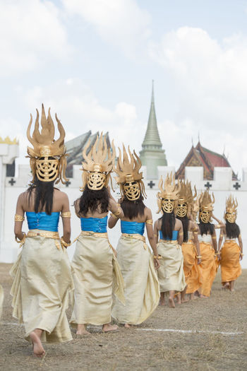 Rear View Of Women Wearing Traditional Costumes While Walking In Row Outside Temple