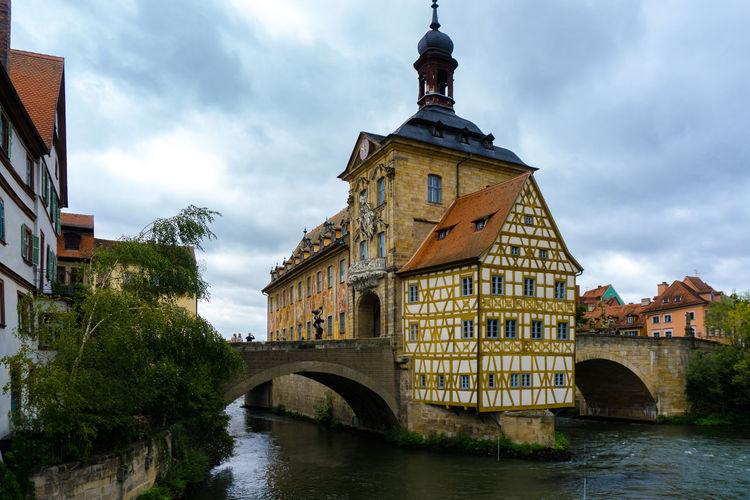 Arch Bridge Over River Amidst Buildings Against Sky
