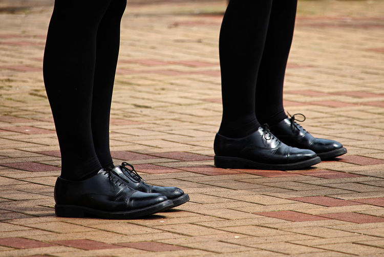 Low section of people in black shoes and socks standing on footpath