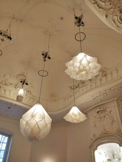 Low angle view of illuminated chandelier hanging on ceiling