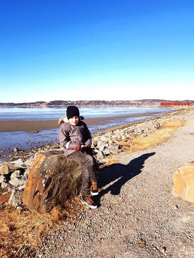 Boy sitting on rock at beach against clear sky