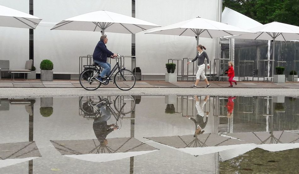 Double Sunshade Parasols Reflections Water People Women Child Running Child Summer White White Color Outdoors Bregenz Streetphotography Street Streetrestaurant Streetcafe Gastronomy Bicycle Biking City Urbangeometry Reflection Lake