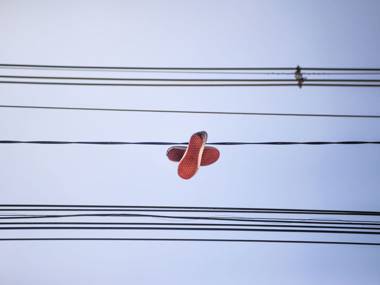 show hanging on city wires Cable Low Angle View Electricity  Power Line  No People Sky Hanging Red Wire Shoe Shoe Strings