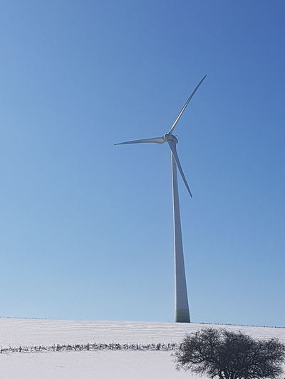 Low angle view of wind mill against clear blue sky