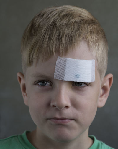 Caucasian boy with a sealed plaster wound on his forehead Boy Boys Caucasian Childhood Close-up Focus On Foreground Forehead Front View Green Color HEAD Headshot Human Face Indoors  Innocence Leisure Activity Lifestyles Looking Person Plaster Sealed Toddler  Wound