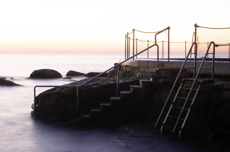 Architecture Beach Beauty In Nature Clear Sky Horizon Horizon Over Water Land Nature No People Outdoors Railing Scenics - Nature Sea Sky Staircase Sunset Tranquil Scene Tranquility Water