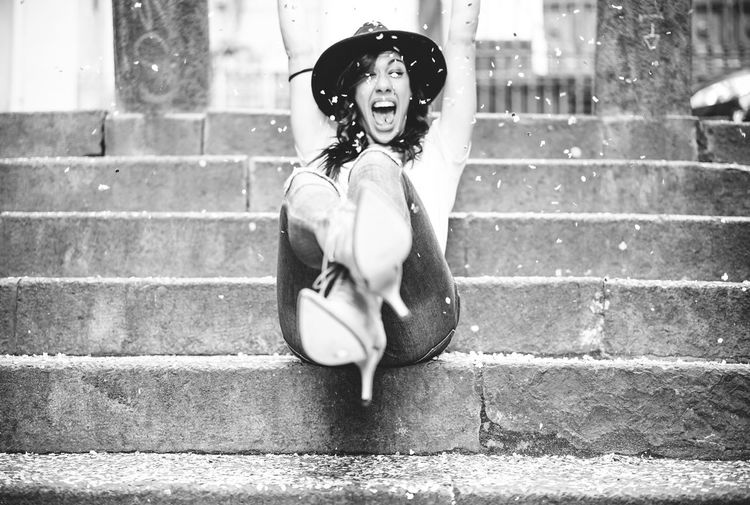 Portrait Of Excited Woman Screaming While Sitting On Steps