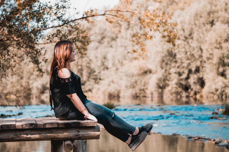 Young woman sitting by tree against water