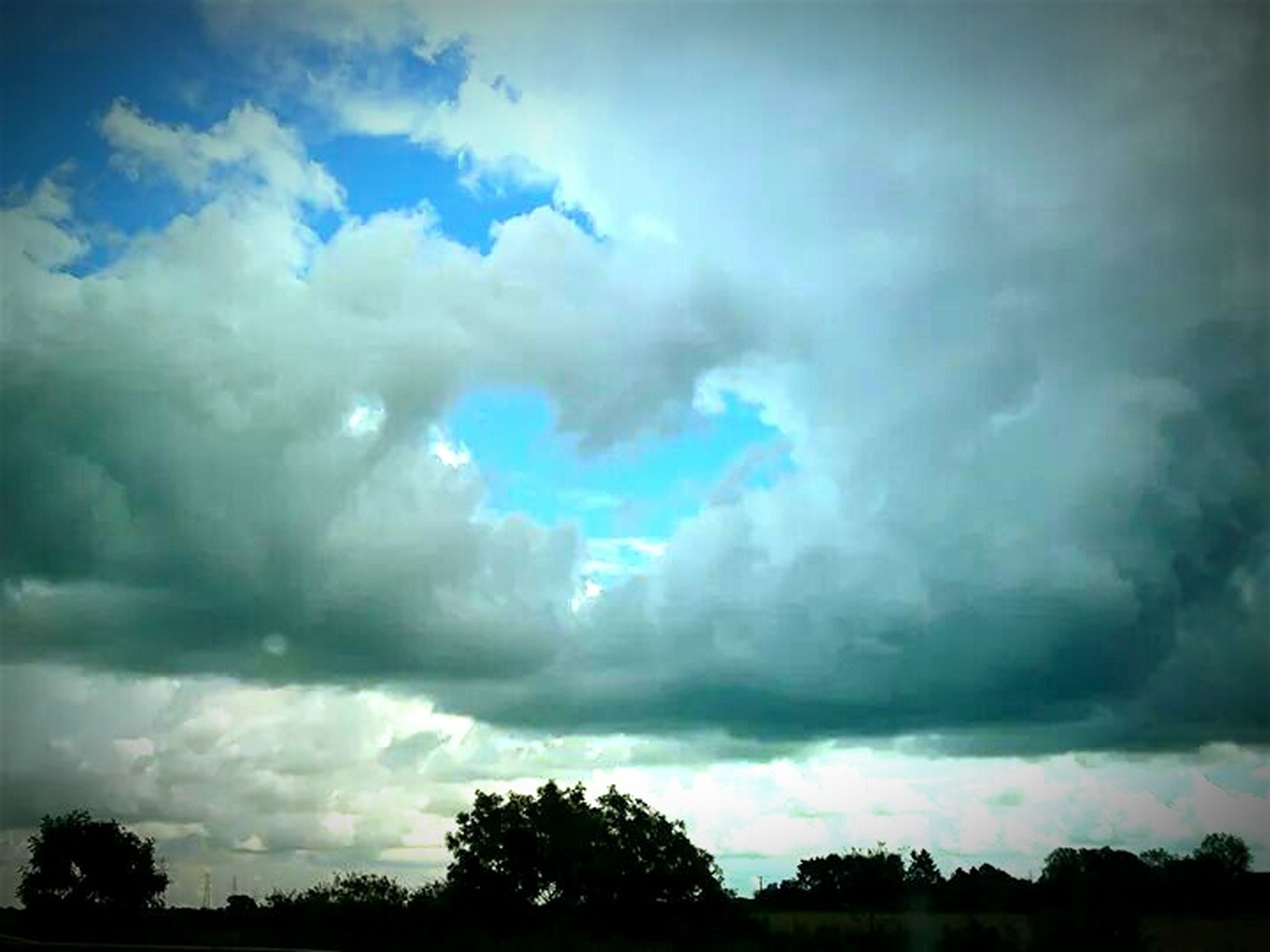 sky, cloud - sky, tree, cloudy, tranquility, beauty in nature, scenics, tranquil scene, silhouette, weather, nature, low angle view, overcast, storm cloud, cloud, cloudscape, dramatic sky, idyllic, dusk, atmospheric mood