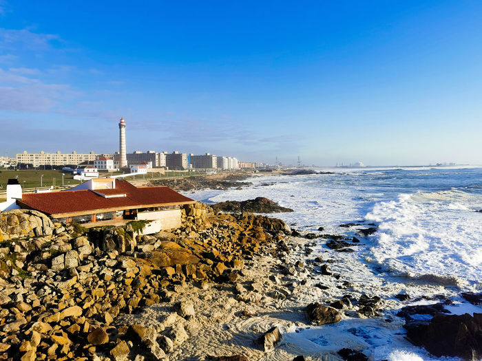 Scenic view of sea by buildings against blue sky