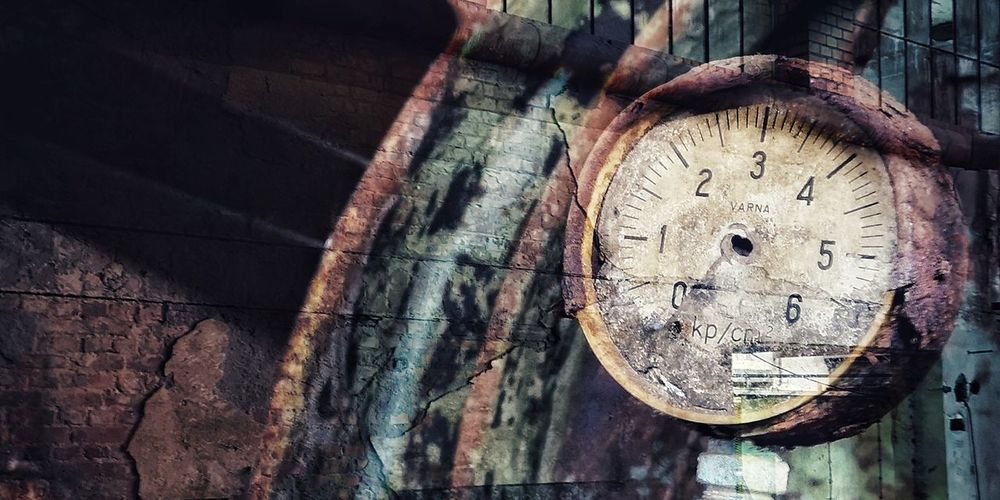 Low angle view of clock on wood against wall