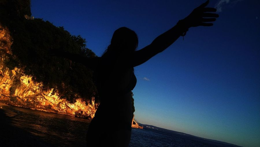 Silhouette woman by sea against clear sky during sunset